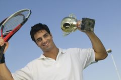 Male Tennis Player raising tennis rackets and Trophy portrait Royalty Free Stock Image