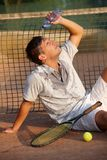 Male tennis player refreshing himself. By water, sitting on ground Royalty Free Stock Images