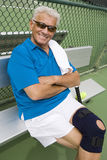 Male Tennis Player Relaxing On Bench. Portrait of a happy senior man relaxing on bench after playing tennis Stock Images