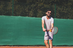 Male tennis player serving the ball. Young man playing tennis on the open court on a sunny day Royalty Free Stock Images