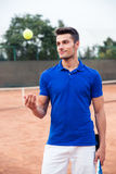 Male tennis player standing outdoors Stock Images