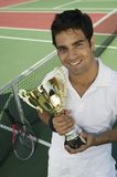 Male Tennis Player standing on tennis court. Holding trophy, portrait, high angle view Royalty Free Stock Image
