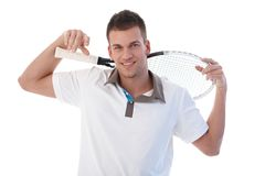 Male tennis player taking a break smiling. Young male tennis player taking a break, smiling, holding tennis racket Royalty Free Stock Photos