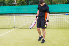 Male tennis player throws the ball after a match at tennis court. Male tennis player wearing a sportswear and holding a racket throws the ball after a match at Stock Photos
