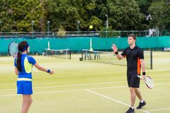 Male tennis player throws the ball to his female partner after a. Match at tennis court at early morning, beautiful forest area as background Stock Photos
