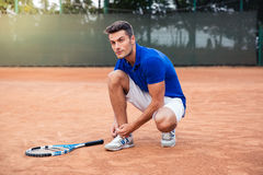 Male tennis player tying shoelaces. Handsome male tennis player tying shoelaces outdoors Royalty Free Stock Photos