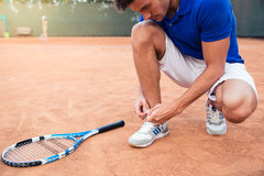Male tennis player tying shoelaces. Outdoors Stock Image