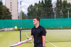 Male tennis player warming up before tennis match. Male tennis player wearing a sportswear warming up before tennis match on a court outdoor in summer or spring Stock Image
