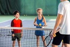 Male tennis trainer teaching children Royalty Free Stock Image