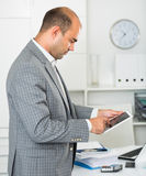 Male testing modern middle size touchpad. In the office Stock Photography