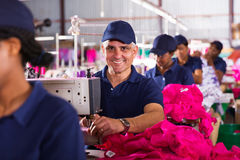 Male textile worker. Middle aged male textile worker sewing in clothing factory Royalty Free Stock Photos