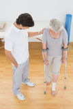 Male therapist assisting disabled senior patient to walk stock image