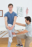 Male therapist assisting a man with stretching exercises. Male therapist assisting a happy young men with stretching exercises in the medical office Royalty Free Stock Images