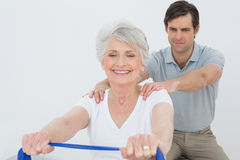 Male therapist assisting senior woman with exercises Royalty Free Stock Photos