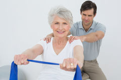 Male therapist assisting senior woman with exercises Stock Photography