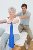 Male therapist assisting senior woman with exercises Stock Photos
