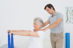 Male therapist assisting senior woman with exercises Royalty Free Stock Image