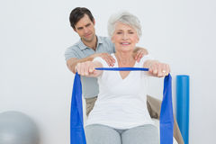 Male therapist assisting senior woman with exercises Royalty Free Stock Photography