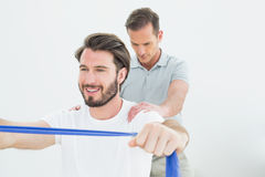 Male therapist assisting a smiling man with exercises. Male therapist assisting a smiling young men with exercises over white background Royalty Free Stock Images