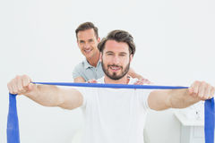 Male therapist assisting young man with exercises Royalty Free Stock Image