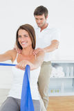 Male therapist assisting young woman with exercises. Male therapist assisting young women with exercises in the medical office Royalty Free Stock Images