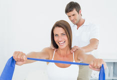 Male therapist assisting young woman with exercises. Male therapist assisting young women with exercises in the medical office Stock Photos