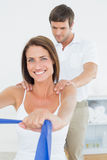 Male therapist assisting young woman with exercises. Male therapist assisting young women with exercises in the medical office Stock Photo
