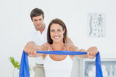 Male therapist assisting young woman with exercises. Male therapist assisting young women with exercises in the medical office Royalty Free Stock Image
