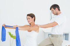 Male therapist assisting young woman with exercises. Male therapist assisting young women with exercises in the medical office Stock Photography
