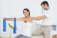 Male therapist assisting young woman with exercises. Male therapist assisting young women with exercises in the medical office Stock Images