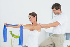 Male therapist assisting young woman with exercises Stock Photography