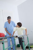 Male therapist with boy in parallel bars Royalty Free Stock Photos