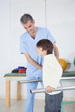 Male therapist with boy in parallel bars Stock Photos