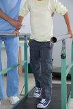 Male therapist with boy in parallel bars Royalty Free Stock Image