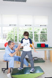 Male therapist with boy in rehab. Man therapist with boy in rehab Stock Photography