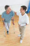 Male therapist and disabled patient with reports. High angle view of a male therapist and disabled patient with reports in the gym at hospital Stock Photo