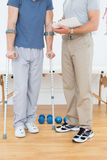 Male therapist and disabled patient with reports. Low section of a male therapist and disabled patient with reports in the gym at hospital Stock Photo