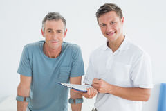 Male therapist and disabled patient with reports. Portrait of a male therapist and disabled patient with reports in the gym at hospital Stock Image