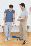 Male therapist discussing reports with a disabled patient. Full length of a male therapist discussing reports with a disabled patient in the gym at hospital Royalty Free Stock Image