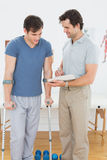 Male therapist discussing reports with a disabled patient. In the gym at hospital Stock Images