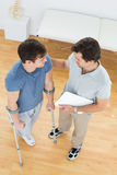 Male therapist discussing reports with a disabled patient. High angle view of a male therapist discussing reports with a disabled patient in the medical office Royalty Free Stock Photos