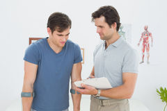 Male therapist discussing reports with a disabled patient. In the medical office Royalty Free Stock Image