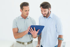 Male therapist discussing reports with a disabled patient. In the medical office Stock Images