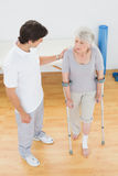 Male therapist in discussion with a disabled senior patient. In the gym at hospital Stock Photos