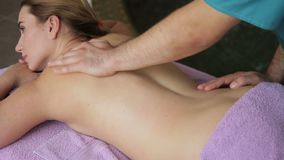 Male therapist does back massage of lying woman in spa salon.