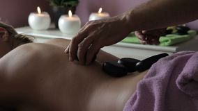 Male therapist does back massage with stones in spa center. He applies neatly black hot rocks on womans skin, which lies on stomach and presses them with hands stock footage