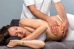 Male therapist doing physical belly treatment on pregnant woman. Royalty Free Stock Images