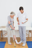 Male therapist examining disabled senior patient leg. In the gym at hospital Stock Images