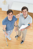 Male therapist gesturing thumbs up with disabled patient. High angle portrait of a male therapist gesturing thumbs up with disabled patient in the medical office Stock Image