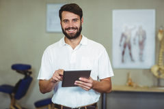 Male therapist holding digital tablet in clinic. Portrait of male therapist holding digital tablet in clinic Royalty Free Stock Image